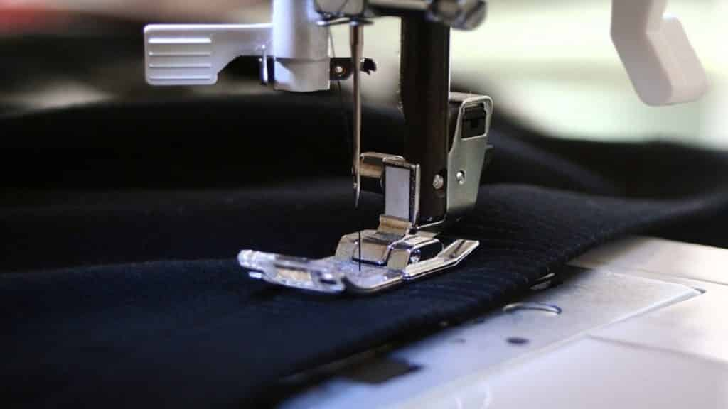 A sewing machine is being used to stitch a black fabric